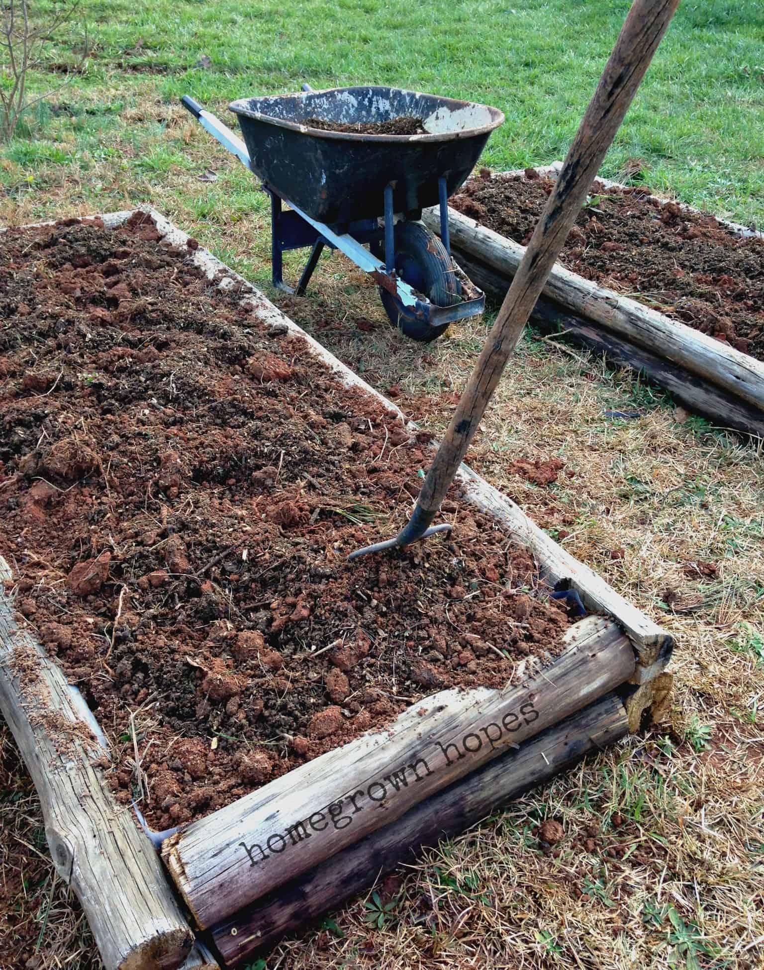 wheelbarrow and pitchfork in raised garden bed full of fresh dirt
