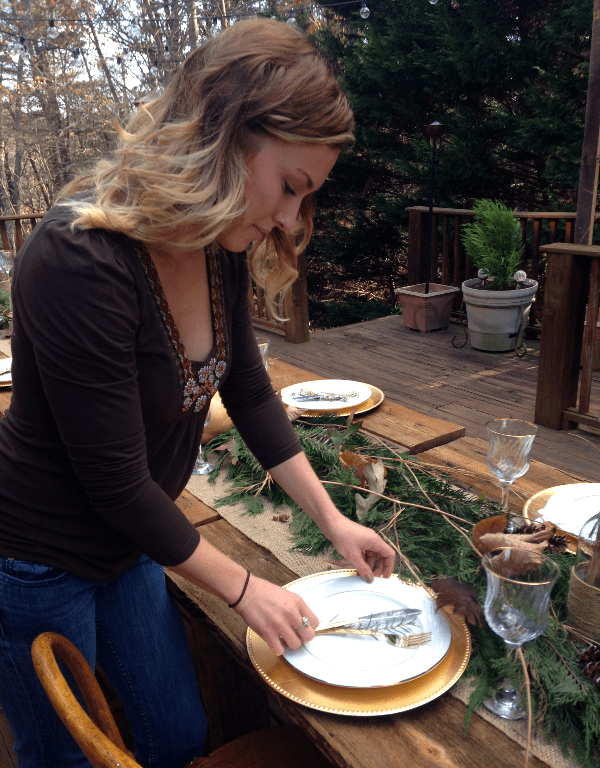 woman creating rustic outdoor thanksgiving table decor