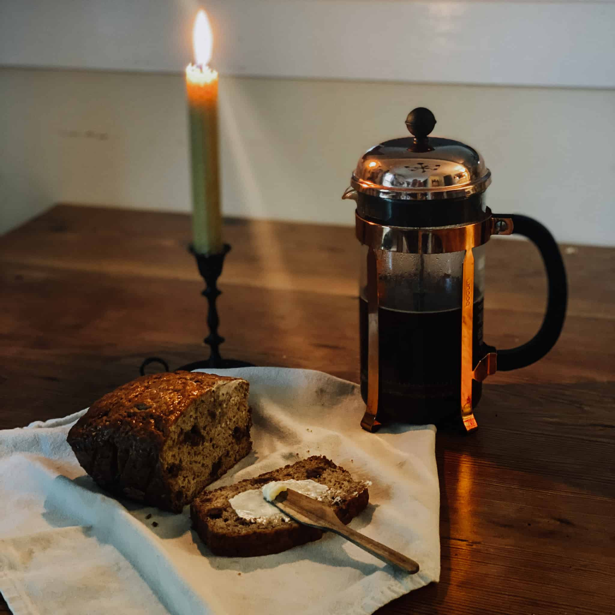 French press coffee and homemade bread by candlelight