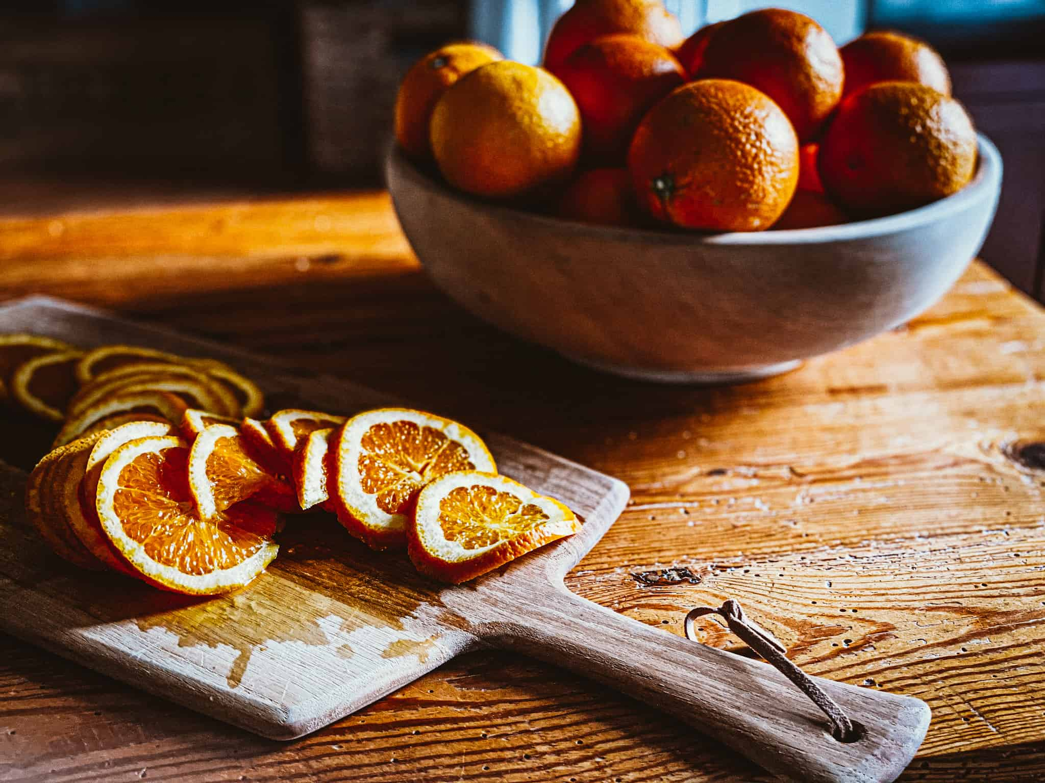 oranges in wooden bowl and sliced oranges on wooden cutting board