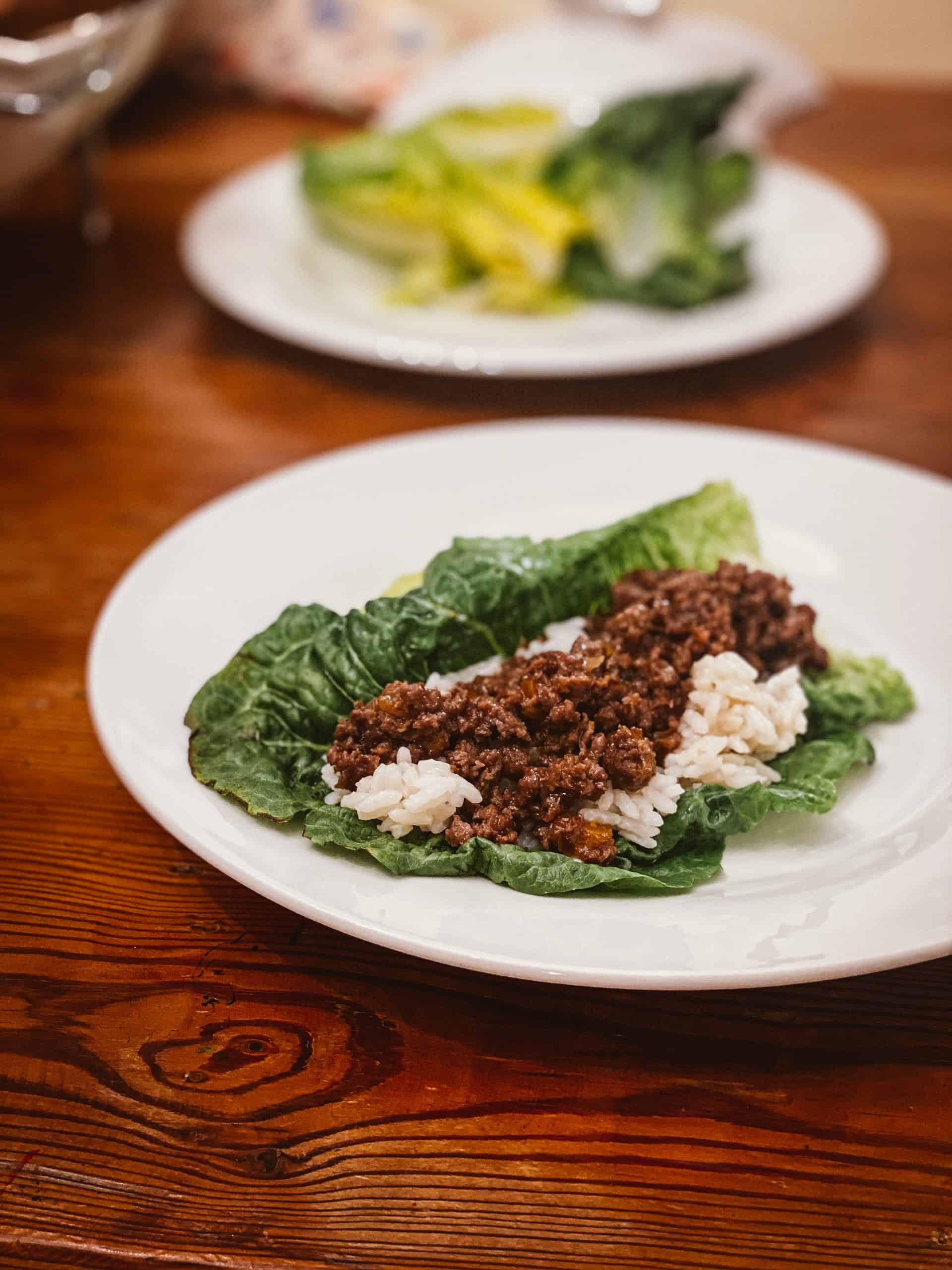 lettuce wraps on white plate with ground venison and rice