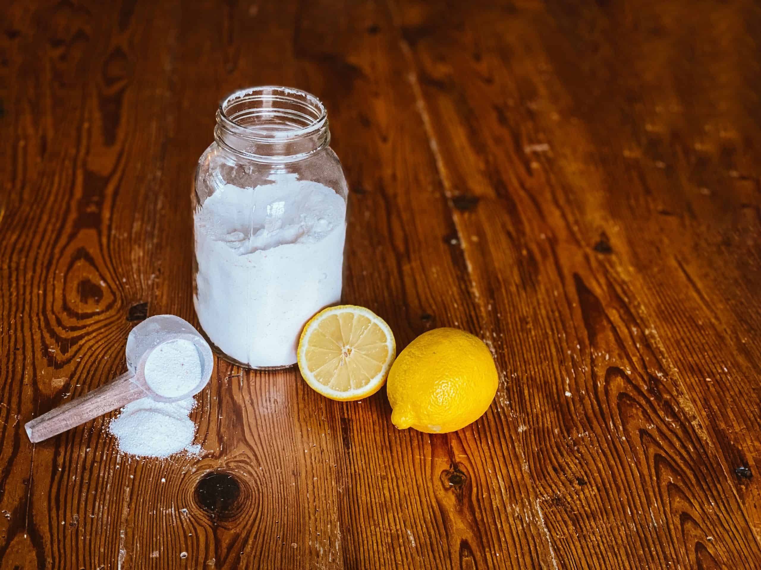 dishwashing detergent powder in mason jar with lemons and wooden scoop