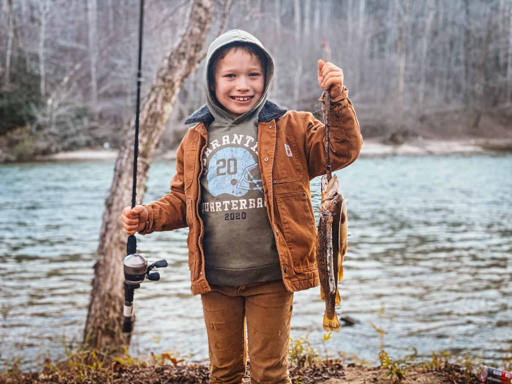 boy by river with fresh caught trout on stringer