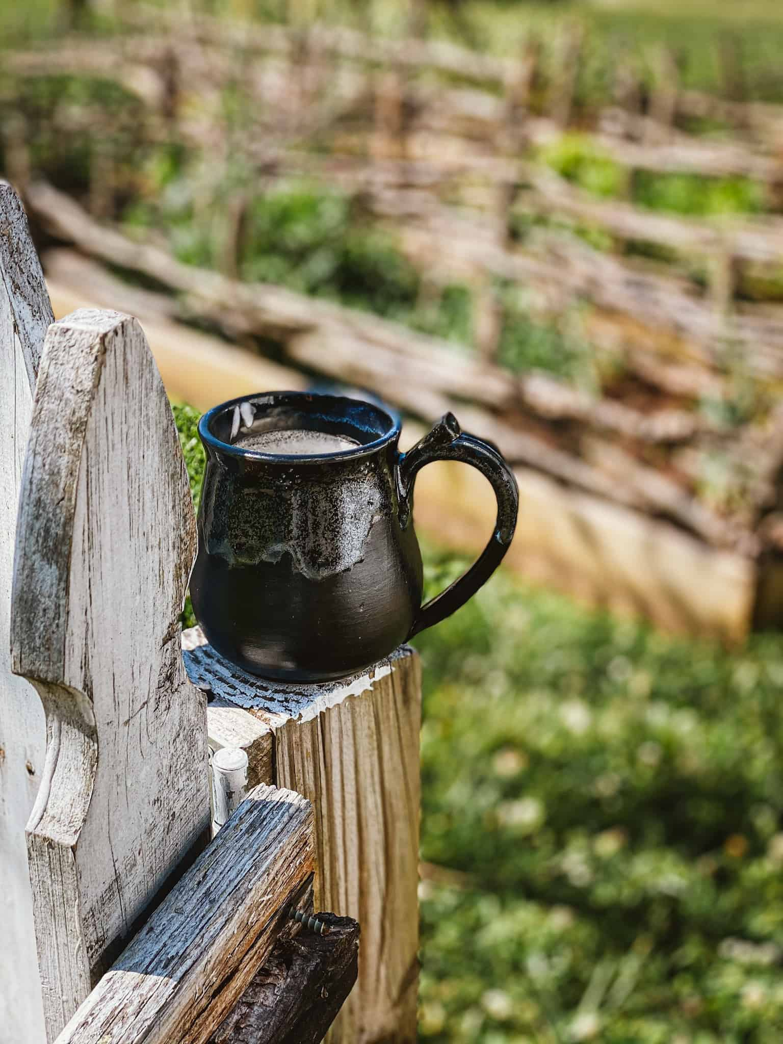 black pottery coffee mug on rustic white picket fence with spring cottage garden in background